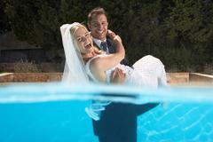 Groom carrying bride in pool Kuvituskuvat