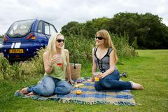 Young women pick-nicking by electric car Stock Photos