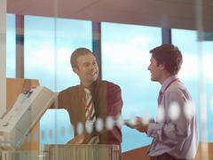 Two men at photocopier Stock Photos
