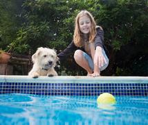 Girl with dog by pool Stock Photos