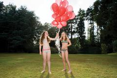 Two girls with red balloons - stock photo
