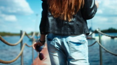 Young sexy Caucasian girl walking on a pier with boats - stock footage