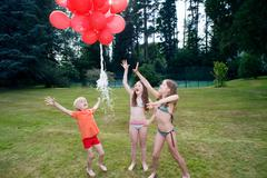 Kids letting go red balloons - stock photo