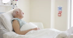 4K Caring medical worker in hospital talking to elderly man at his bedside Stock Footage