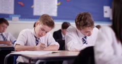 4k, A young student raises his hands to ask a question in a classroom. Stock Footage