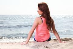 Beach holidays woman enjoying summer sun sitting sand looking happy - stock photo