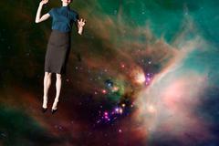 Businesswoman in outer space - stock photo