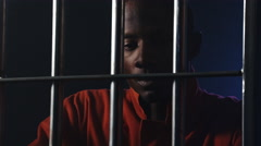Sad african american man in jail looking out his prison cell doors Stock Footage