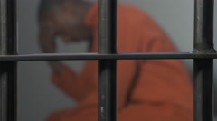 Modern Prison or Jail Scene - man pondering life in his cell Stock Footage