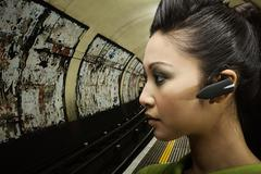 A woman wearing a bluetooth headset - stock photo