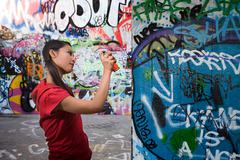 A young woman spraying graffiti Stock Photos