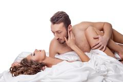 Erotica. Man passionately hugging woman in bed Stock Photos