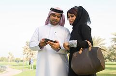 A young man showing his wife his cell phone - stock photo