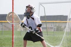 Junior lacrosse player in goal - stock photo