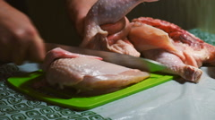 Cutting a chicken on a board - stock footage
