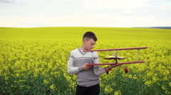 Handsome child holds homemade airplane on the canola background. 4K - stock footage