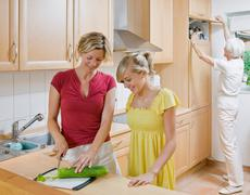 Young girl and women preparing meal Stock Photos
