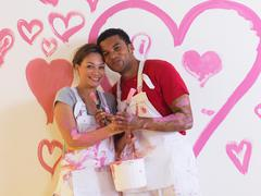 Girl and man in front of pink hearts. - stock photo