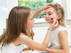 Girl putting make-up on friend - stock photo