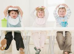 Children with food bowls on their head. Stock Photos