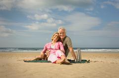 Couple sat on a beach Stock Photos