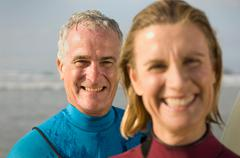 Couple wearing wetsuits on a beach Stock Photos