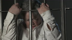 Screaming woman holding jail bars in prison cell Stock Footage