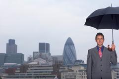 Mann with umbrella city scape - stock photo