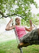 Young girl on a tree swing Stock Photos
