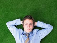 Businessman lying on grass Stock Photos