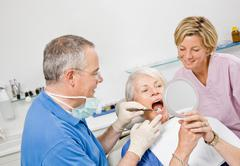 Dentist and assistant working on patient Stock Photos