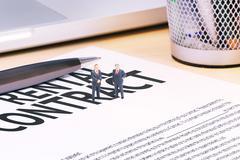 Businessman miniatures on document - stock photo