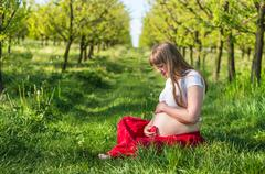 Pregnant young girl sit on grass in the garden with a plush heart - stock photo