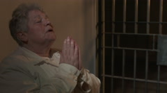 Woman praying for forgiveness in jail cell Stock Footage