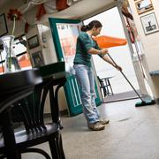 Woman sweeping in a cafe Stock Photos