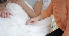 4K Elderly man in hospital visited by his daughter, chatting & holding his hand Stock Footage