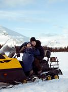 Mother and baby on Snowmobile - stock photo