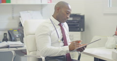 4K Doctor sitting alone in office writing notes on patient medical record - stock footage
