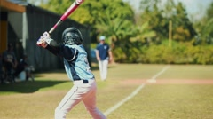 Slow motion of boy batting at baseball game and runner on third base - stock footage