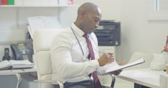 4K Doctor sitting alone in office writing notes on patient medical record Stock Footage