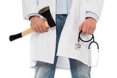 Evil medic holding a small axe and stethoscope - stock photo