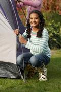 Two girls erecting tent - stock photo