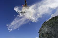 Snowboarder jumping off a rock - stock photo