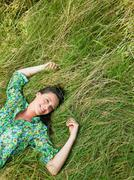Woman laying down in a field Stock Photos