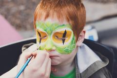 Child face painting process at redhead boy Stock Photos