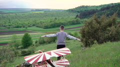 Boy running down the mountain, toy helicopter in front of. 4k - stock footage