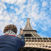 Man taking picture of Eiffel tower - stock photo