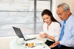 Woman and senior man looking at papers Stock Photos