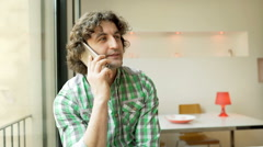 Man talking on cellphone in the flat and looking worried, steadycam shot Stock Footage