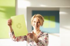 Woman looking at green sheet with logo Stock Photos